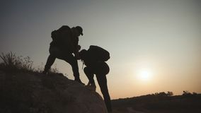 pares que caminan ayuda silueta en monta?as Los pares del trabajo en equipo que caminan, se ayudan, conf?an en la ayuda, puesta d almacen de metraje de vídeo