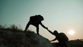 pares que caminan ayuda silueta en monta?as Los pares del trabajo en equipo que caminan, se ayudan, conf?an en la ayuda, puesta d metrajes