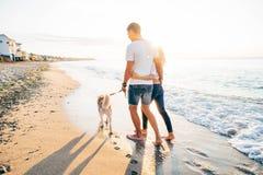 Pares que caminan con los perros en la playa Imagen de archivo