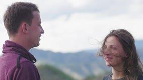 Pares que caminan contra el contexto de las montañas honeymoon beso en el fondo de las montañas el viento se convierte almacen de metraje de vídeo