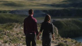 Pares que caminan contra el contexto de las montañas honeymoon manos y paseo del control del hombre y de la mujer en naturaleza P almacen de video