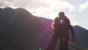 Pares que caminan contra el contexto de las monta?as honeymoon beso en el fondo de las monta?as el viento se convierte almacen de metraje de vídeo