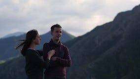 Pares que caminan contra el contexto de las monta?as honeymoon beso en el fondo de las monta?as el viento se convierte metrajes