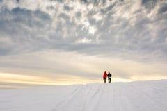Pares que caminan en la montaña nevada Imágenes de archivo libres de regalías