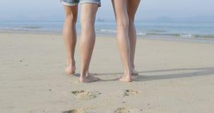 Pares que caminan en la playa al mar, a la vista posterior de la parte posterior del primer de las piernas, al hombre y a la muje almacen de metraje de vídeo