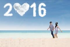 Pares que caminan en la playa con los números 2016 Imagen de archivo libre de regalías