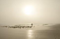 Pares que caminan en la playa de niebla hermosa Fotografía de archivo libre de regalías