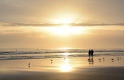 Pares que caminan en la playa en la salida del sol Imagen de archivo libre de regalías