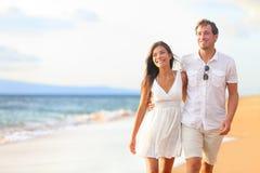 Pares que caminan en la playa en viaje romántico Imagenes de archivo
