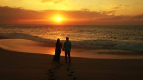 Pares que caminan en la playa que disfruta de vacaciones de la puesta del sol en viaje romántico de la luna de miel