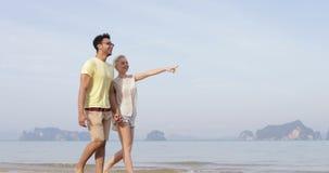 Pares que caminan en la playa que sostiene las manos que hablan, el hombre joven y el finger del punto de la mujer, turistas el v
