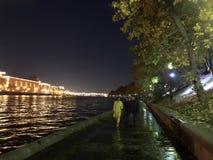 Pares que caminan en parque de la ciudad cerca del río foto de archivo libre de regalías