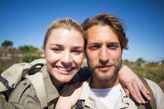 Pares que caminan felices que caminan en el terreno de la montaña que sonríe en la cámara Fotografía de archivo libre de regalías