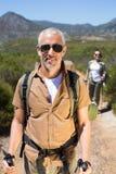 Pares que caminan felices que caminan en rastro de montaña Fotografía de archivo