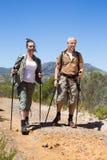 Pares que caminan felices que caminan en rastro de montaña Foto de archivo libre de regalías