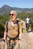 Pares que caminan felices que caminan en rastro de montaña Foto de archivo
