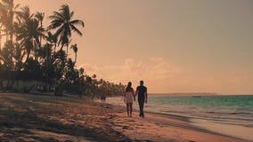 Pares que caminan a lo largo de la playa del verano en la puesta del sol metrajes