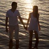 Pares que caminan por el mar en la puesta del sol fotografía de archivo