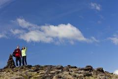 Pares que caminham apontar por Pedra Pilha na montanha Fotos de Stock Royalty Free