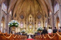Pares que casam-se em uma igreja gótico bonita imagem de stock