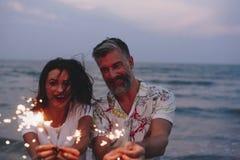 Pares que celebran con las bengalas en la playa imágenes de archivo libres de regalías
