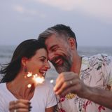Pares que celebran con las bengalas en la playa fotografía de archivo