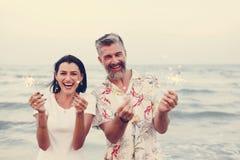 Pares que celebran con las bengalas en la playa fotos de archivo libres de regalías