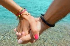 Pares que celebran las manos en el mar Imágenes de archivo libres de regalías