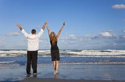 Pares que celebran los brazos levantados en una playa Fotografía de archivo