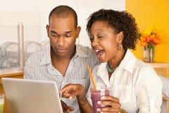 Pares que cenan hacia fuera usando una computadora portátil Imagenes de archivo