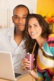Pares que cenan hacia fuera usando una computadora portátil Imagen de archivo