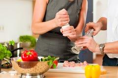 Pares que cocinan junto en cocina Imagen de archivo