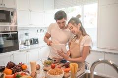 Pares que cocinan junto en la cocina en casa mirada de la PC de la tableta Imagen de archivo libre de regalías