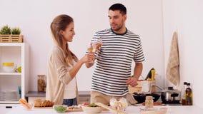 Pares que cocinan la comida y que beben el vino en casa almacen de metraje de vídeo