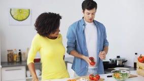 Pares que cocinan la comida y que hacen juegos malabares los tomates en casa almacen de video