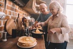 Pares que cocinan las crepes en cocina en casa Imagen de archivo libre de regalías