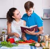 Pares que colocan la tabla cercana con las verduras Imagen de archivo libre de regalías