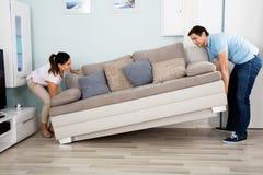 Pares que colocan a Sofa In Living Room imagen de archivo