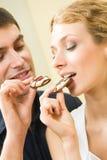 Pares que comem bolinhos junto Imagem de Stock