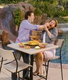 Pares que comem no poolside Imagens de Stock