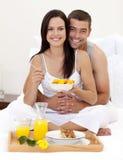 Pares que comem o pequeno almoço nutritivo na cama Fotografia de Stock