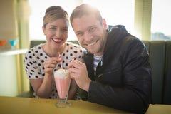 Pares que comen batido de leche en restaurante Imagen de archivo