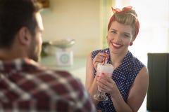 Pares que comen batido de leche en restaurante Imagen de archivo libre de regalías