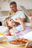 Pares que comen el desayuno en cama con la tableta de papel y de Digitaces Foto de archivo