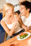 Pares que comen en la cocina Imagen de archivo