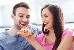 Pares que comen la pizza Imágenes de archivo libres de regalías