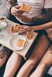 Pares que comen tostadas en cama Fotografía de archivo