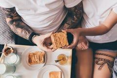 Pares que comen tostadas en cama Imagen de archivo libre de regalías