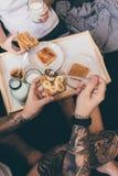 Pares que comen tostadas en cama Fotografía de archivo libre de regalías