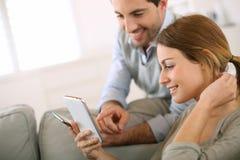 Pares que comparan smartphones en casa Imagenes de archivo